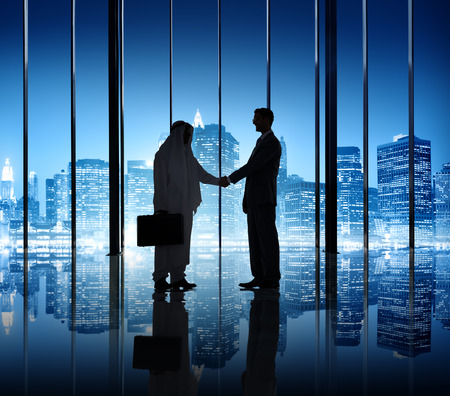 Two businessmen shaking hand in the office building. photo