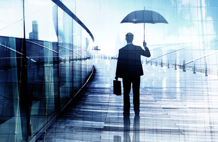 Depressed Businessman Standing While Holding an Umbrella Фото со стока