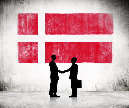national trust: Two Businessmen Shaking Hands With Denmark Flag As A Background