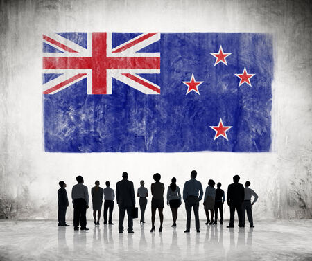 Silhouettes of Business People Looking at the Flag of New Zealand photo