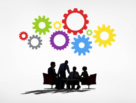 Silhouettes of Business People Having a Meeting and Gears Above photo
