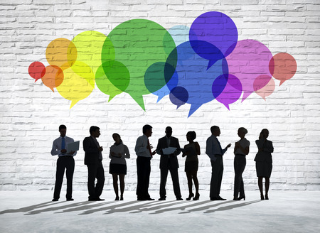 mixed age: Group of business people discussing with colorful speech bubbles above them.