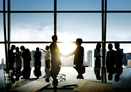 business relationship: Group of business people and men handshake reflected onto table with documents.