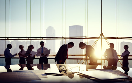 business activity: Group of business people and men bowing reflected onto table with documents.