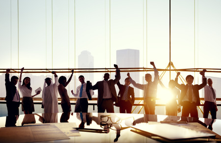 Group Of Business People With Their Arms Raised In Board Room