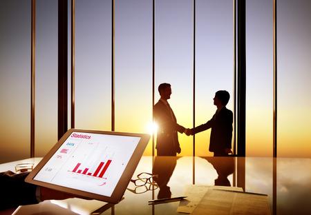 dandose la mano: Siluetas de dos hombres de negocios que sacuden las manos juntas en una sala de juntas Foto de archivo