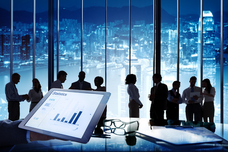 business meeting: Group of business people in a conference room and a tablet with statistics.