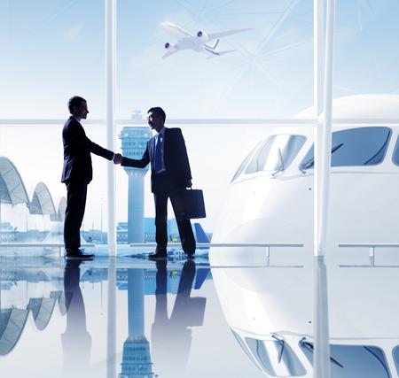 2 人のビジネスマンは空港で握手します。