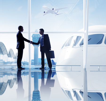 Two businessmen shaking hands in an airport.