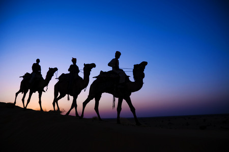 Three indigenous men riding camel through the dimly lit desert. photo