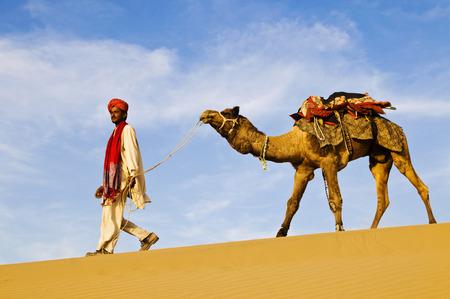 thar: Indigenous Indian man walking through the desert with his camel.