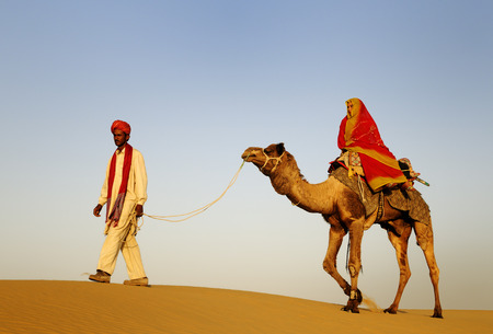 Indigenous Indian man and woman traveling through the desert riding camel. photo
