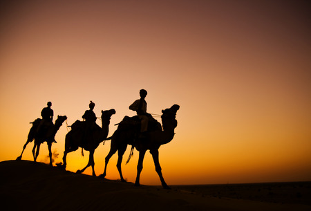 Indigenous Indian men riding through the desert with their camel. photo