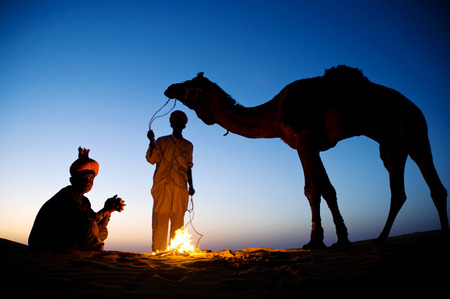 Two indigenous Indian men resting by the bon fire with their camel. photo