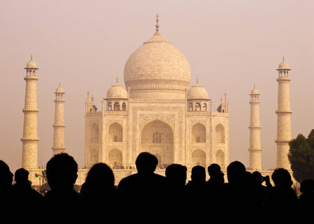 View of Taj Mahal with tourist silhouettes.