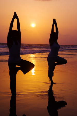 Serene people in the beach doing yoga in the sunset.  photo