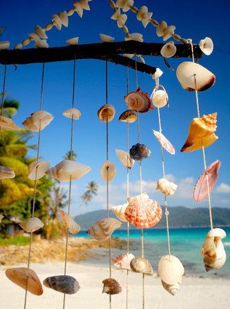 wind chime: Sea shell chime overlooking a tropical lagoon. Stock Photo