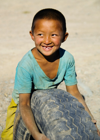 independent mongolia: Asian boy with a beautiful smile playing with a tyre.