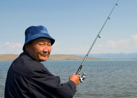 independent mongolia: Mongolian man fishing in one of many Mongolia lakes. Stock Photo