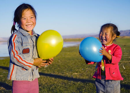 independent mongolia: Asian girls playing by a lake.