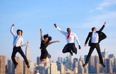 jumping: Hombres de negocios exitosos felices que celebran saltando en Nueva York.