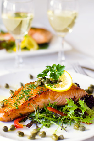 Grilled salmon fillet with vegetables and a glass of white wine.