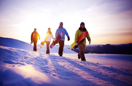 alpine skiing: Group of snowboarders on top of the mountain.