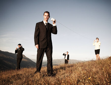 Business people communicate through the paper cup phone outdoors. photo