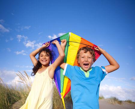 papalote: Niños alegres jugando con una cometa al aire libre