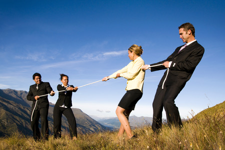 Business mensen die touwtrekwedstrijd spelen op de bergen.