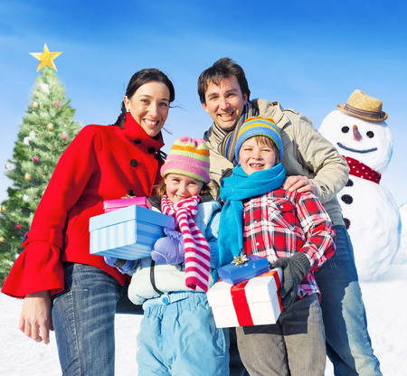 Family posing for camera having christmas tree and a snowman as a background. photo