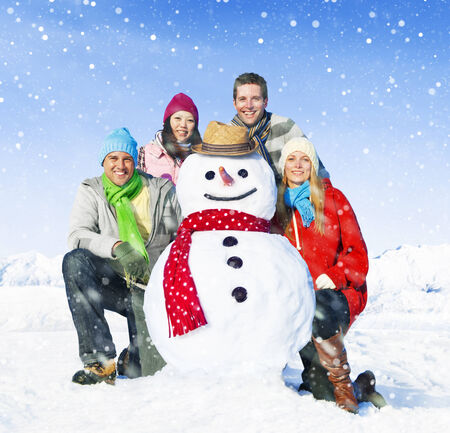Group of friends posing with a snowman. photo