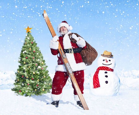 Santa claus holding sack and skis next to a christmas tree. photo