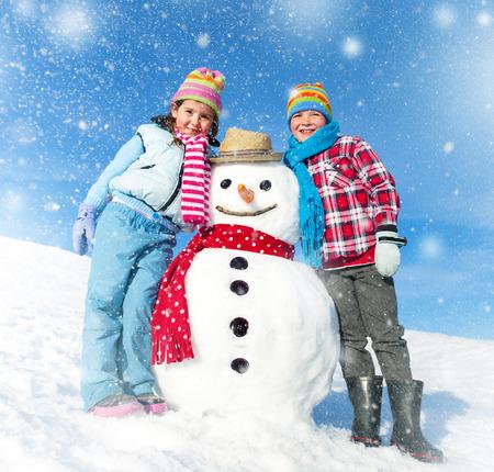 Children having fun with a Snowman.  photo