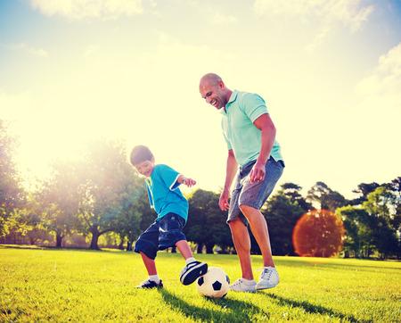 padres: Niño jugando al fútbol con su padre.