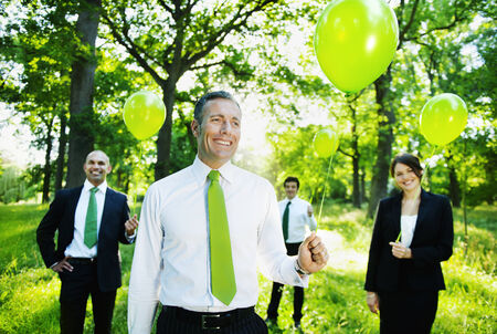 Eco-friendly business people holding green balloons in the woods. photo