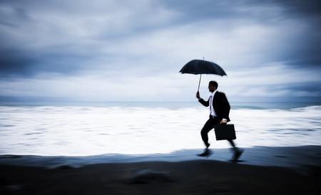pressured: Worried Businessman Running by the Beach Stock Photo