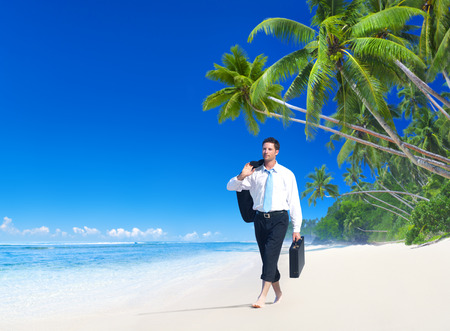 Businessman walking along the tropical beach. photo