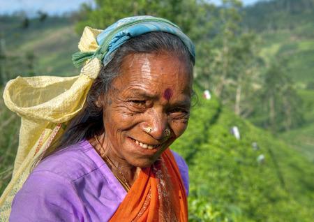 nose picking: Tea picker smiles at the camera.