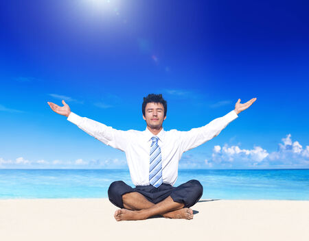 Businessman meditating on the beach. photo