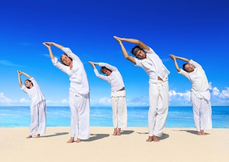 man made structure: People performing yoga on the beach. Stock Photo