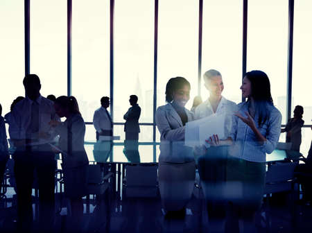 business person: Silhouettes Of Multi-Ethnic Group Of Business People Working Together In A Board Room Stock Photo