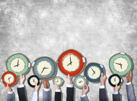 administración del tiempo: Grupo de manos que sostienen Reloj Foto de archivo