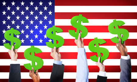 fluctuation: Multi-Ethnic Hands Holding Dollar Signs With Flag Of USA For The Background. Stock Photo