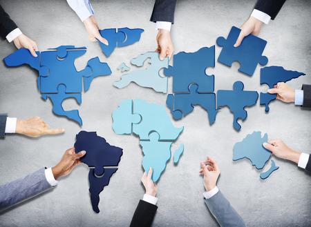 Grupo de hombres de negocios con Jigsaw Puzzle Formando en Mapa del Mundo Foto de archivo - 34537347