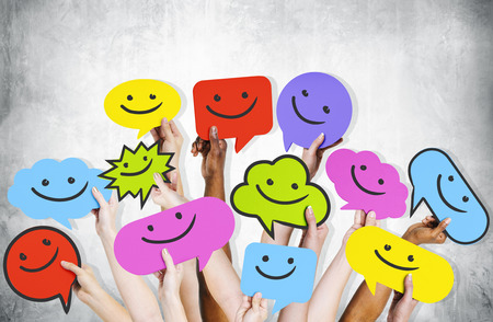 Hands holding smiley faces icons. Stock Photo