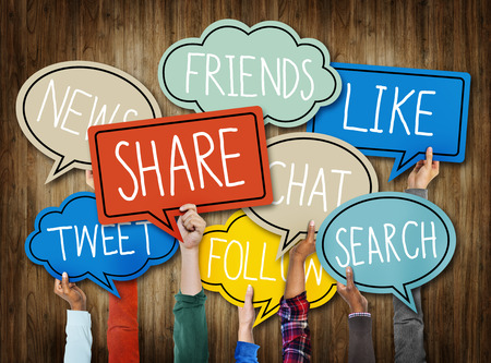 interaccion social: Manos que sostienen Burbujas del discurso con palabras de los medios sociales Foto de archivo