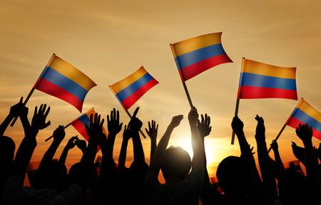 la bandera de colombia: Siluetas de personas que tienen la bandera de Colombia Foto de archivo