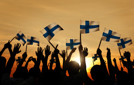Silhouettes of People Holding the Flag of Finland photo
