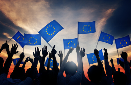gente saludando: Grupo de personas que ondeaban banderas de la Uni�n Europea en Contraluz